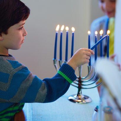 Boy lighting candle at hanukkah